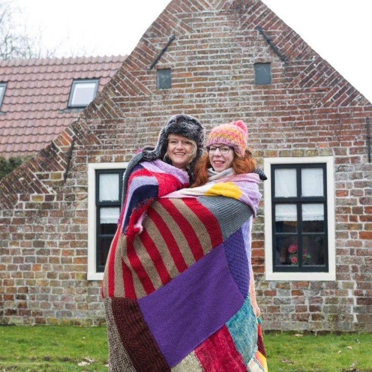 Initiatiefnemers Brenda Harsveld van Milieudefensie (links) en Agnes Bakker (rechts) bij het huisje in Rottum met een deel van de deken (foto Annet Eveleens)